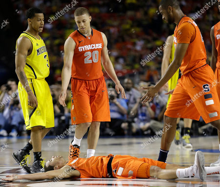Syracuse's Michael Carter-Williams (1) lies on the court as Syracuse's Brandon Triche (20) helps him during the second half of the NCAA Final Four tournament college basketball semifinal game against Michigan, in Atlanta