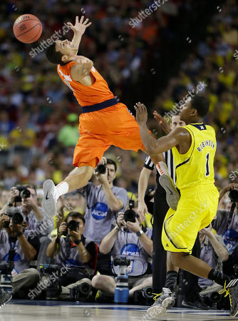 Michigan's Glenn Robinson III (1) and Syracuse's Michael Carter-Williams (1) vie for a loose ball during the first half of the NCAA Final Four tournament college basketball semifinal game, in Atlanta