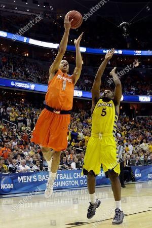 Junior Cadougan, Michael Carter-Williams Syracuse guard Michael Carter-Williams (1) shoots past Marquette guard Junior Cadougan (5) during the second half of the East Regional final in the NCAA men's college basketball tournament, in Washington