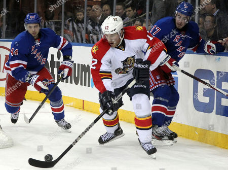 Jack Skille, Steve Eminger, John Moore Florida Panthers' Jack Skille (12) skates past New York Rangers' Steve Eminger (44) and John Moore (17) during the third period of the NHL hockey game at Madison Square Garden in New York. The Ranges won 6-1