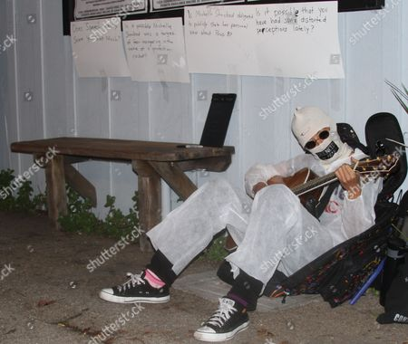 Alternative folk singer Michelle Shocked strums her guitar outside Moe's Alley nightclub in Santa Cruz, Calif., after her show was canceled because she made an anti-gay slur earlier this month. Shocked had her face covered and her mouth taped shut. She dressed in a white disposable safety suit and invited people to write on it