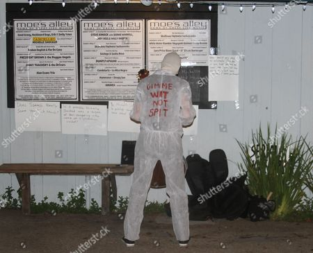Alternative folk singer Michelle Shocked reads signs outside Moe's Alley nightclub in Santa Cruz, Calif., after her show was canceled because she made an anti-gay slur earlier this month. Shocked had her face covered and her mouth taped shut. She dressed in a white disposable safety suit and invited people to write on it