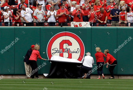 Members of the Musial family unveil a logo on the outfield wall during a ceremony honoring former St. Louis Cardinals great Stan Musial before the start of a baseball game between the St. Louis Cardinals and the Cincinnati Reds, in St. Louis. Musial died January 19, 2013 at the age of 92