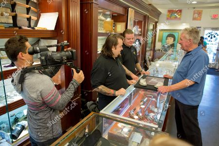 Cameraman Mark Matusiak shoots a scene between Chumlee, second from left, Corey Harrison, and customer Gene McCauliff of Las Vegas, for the reality tv series Pawn Stars, Wednesday, April 3, 2013, in Las Vegas. Pawn sales at the Gold & Silver Pawn Shop bring in about $20 million a year, up from the $4 million a year it made before the show aired.Turning small business owners into stars has become a winning formula for television producers, but the businesses featured in the shows are cashing in, too. Sales explode after just a few episodes have aired, transforming nearly unknown small businesses into household names
