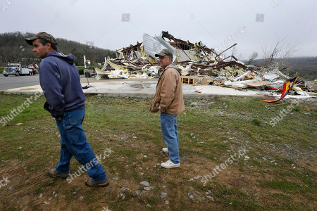 Larry Gammill, left, who attends Botkinburg Foursquare Church, and his friend Tim Parks walk from what is left of the church in Botkinburg, Ark., after a severe storm struck the building late Wednesday. The National Weather Service is surveying areas Thursday to determine whether tornadoes or strong winds caused damage