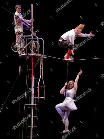 """Bello Nock, Annalise Nock, Zebulon Freicke This photo shows performer Bello Nock, upper right, riding a miniature bicycle on a highwire, as his daughter Annalise Nock hangs below, and adoped son Zebulon Freicke assists, during his """"Bello Mania"""" show at the New Victory Theater in New York. Nock, a seventh-generation circus performer, is never offstage during the 90-minute performance, which combines slapstick clowning with death-defying aerial stunts. He performs through March 31 at the New Victory before moving on to the Canadian side of Niagara Falls and then a 10-week stint at the Beau Rivage Casino in Biloxi, Miss"""