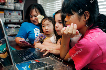 """Guan Ya Smith, GiGi Smith, Macy Jade Smith, Niki Smith Graph, the Smith women, from left, mother Niki Smith, GiGi, 3, Macy Jade, 7 and Guan Ya, 14, use Google Translate on the family laptop to """"speak"""" with their new daughter, Guan Ya, in their Rienzi, Miss., home. The Smiths and their children are using the Google Translate program to communicate almost exclusively with Guan Ya, who is deaf. The family uses iPhones, iPods and a laptop, all loaded with the program to write in either English that translates to Chinese or vice-a-versa"""