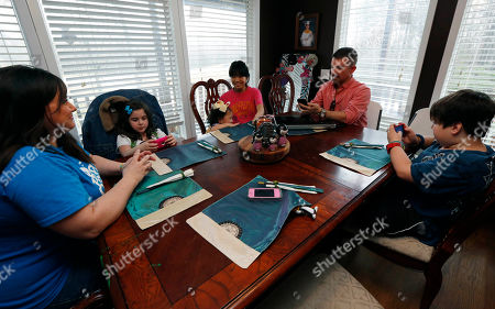 """Guan Ya Smith, GiGi Smith, Colton Smith, Macy Jade Smith, Niki Smith, Phillip Smith Graph, Phillip Smith, right, and wife Niki, left, are using Google Translate on their iPhones to """"speak"""" with their new daughter, 14-year-old Guan Ya, third from right, in their Rienzi, Miss., home. The Smiths and their three other children, Colton, 10, right, GiGi, 3, third from left, and Macy Jade, 7, second from left, are using the program to communicate almost exclusively with Guan Ya, who is deaf. The family uses iPhones, iPods and a laptop, all loaded with the program to write in English that translates to Chinese and Guan Ya responds with Chinese to English"""