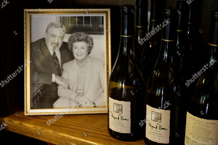 """Stock Image of Bottles of Chardonnay are shown beside of photograph of the late actor Raymond Burr and actress Barbara Hale at Raymond Burr Vineyards in Healdsburg Calif. The star of TV's """"Perry Mason"""" and """"Ironside,"""" also had a passion for wine, which is still celebrated at this small winery in Sonoma County's Dry Creek Valley"""
