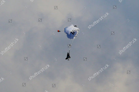 """Swiss pilot Yves Rossy, known as 'Jetman,' the first man in the world to fly a jet-fitted wing, opens his parachute during a performance flight during the 43st Icare Cup paragliding festival in Saint Hilaire du Touvet, French Alps, . The """"Coupe Icare"""" dedicated to free flight, orchestrates all the various types of flying such as hang gliding, paragliding and acrobatic sailplaneing"""