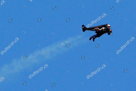 """Swiss pilot Yves Rossy, known as 'Jetman,' the first man in the world to fly a jet-fitted wing, performs a flight during the 43st Icare Cup paragliding festival in Saint Hilaire du Touvet, French Alps, . The """"Coupe Icare"""" dedicated to free flight, orchestrates all the various types of flying such as hang gliding, paragliding and acrobatic sailplaneing"""