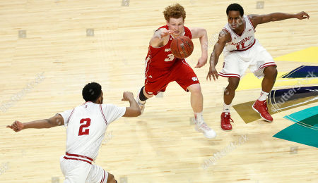 Mike Bruesewitz, Christian Watford, Yogi Ferrell Wisconsin's Mike Bruesewitz goes after a loose ball against Indiana's Christian Watford (2) and Yogi Ferrell (11) during the second half of an NCAA college basketball game at the Big Ten tournament, in Chicago. Wisconsin won 68-56