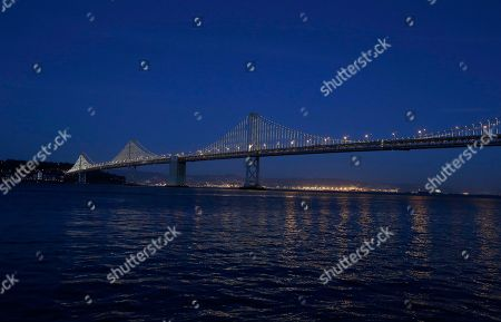 "Lights are turned on along the western half of the San Francisco-Oakland Bay Bridge, seen from San Francisco. Illuminate the Arts said, that private donations and a deal with the Bay Area Toll Authority will allow ""The Bay Lights"" to keep shining on the bridge following an intermission of many months next year. Created by New York artist Leo Villareal, ""The Bay Lights"" consists of 25,000 white lights spaced a foot apart on the span's vertical cables and individually programmed to produce sequences of shifting light"