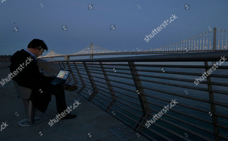 Artist Leo Villareal poses for photographs as he operates lights on the San Francisco-Oakland Bay Bridge on Pier 14 in San Francisco. The San Francisco-Oakland Bay Bridge has been turned into the latest, and by far the biggest, backdrop for New York artist Leo Villareal, who has individually programmed 25,000 white lights spaced a foot apart on 300 of the span's vertical cables to create what is being billed as the world's largest illuminated sculpture