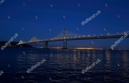 Lights are turned on along the western half of the San Francisco-Oakland Bay Bridge, seen from San Francisco, . The San Francisco-Oakland Bay Bridge has been turned into the latest - and by far the biggest - backdrop for New York artist Leo Villareal, who has individually programmed 25,000 white lights spaced a foot apart on 300 of the span's vertical cables to create what is being billed as the world's largest illuminated sculpture