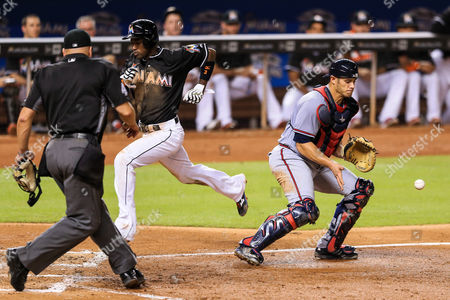 Adeiny Hechavarria, Anthony Recker Miami Marlins shortstop Adeiny Hechavarria (3) scores a run ahead of Atlanta Braves catcher Anthony Recker (20) during the fourth inning of a baseball game, in Miami