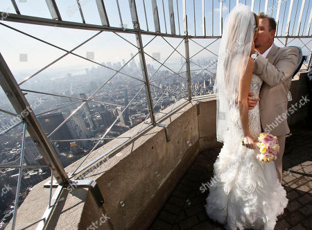 """Newlyweds Danielle Brabham, 39, and Michael Lynch, 41, from Miami Shores, Fla., kiss while posing for pictures on the Empire State Building viewing platform after their Valentine's Day wedding on in New York. Brabham and Lynch were among three couples chosen for the 19th Annual Weddings Event, """"Love is in the Air,"""" designed by celebrity designer Preston Bailey, after submitting their personal love stories to the Empire State Building's Facebook page"""