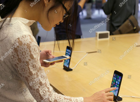 Lisa Gao, from Chicago, compares a new jet black iPhone 7, right, with her iPhone 6 at the Apple Store on Michigan Avenue, in Chicago