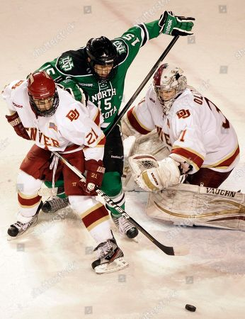 Denver University's Joey Laleggia, left, and goalie Juho Olkinuora, far right, defend their goal against North Dakota's Michael Parks, during the third period of an NCAA hockey match in Denver, . Denver won 5-4