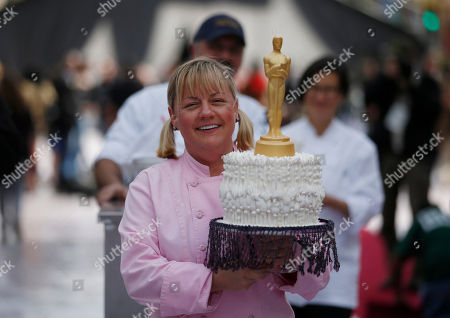 Sherry Yard Sherry Yard, executive pastry chef of Wolfgang Puck's dining group, carries a cake decorated with an Oscar statue as she walks through the red carpet arrival area outside the Dolby Theatre in the Hollywood section of Los Angeles, . The 85th Academy Awards will be held in Los Angeles on Feb. 24