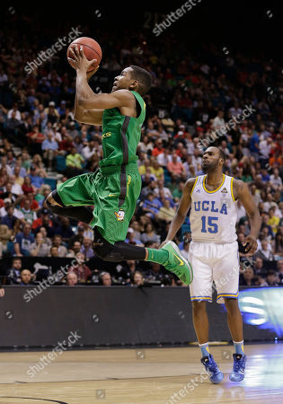Oregon's Dominic Artis shoots against UCLA's Shabazz Muhammad in the first half of the Pac-12 tournament championship NCAA college basketball game, in Las Vegas