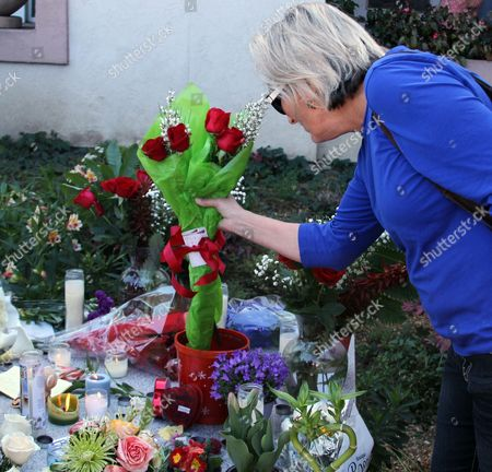 Santa Cruz, Calif., resident Leslie Dwyer adds a bouquet to a growing memorial outside the Santa Cruz Police Department, in honor of two slain police detectives. The detectives, responding to a sexual assault report Tuesday afternoon, were killed at the doorstep of a suspect who was chased down and killed half an hour later