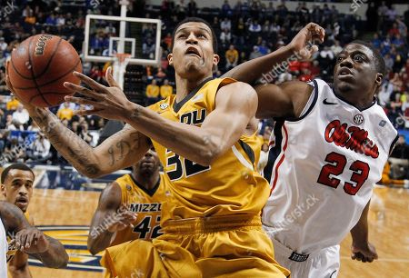 Missouri guard Jabari Brown (32) heads to the basket as Mississippi forward Reginald Buckner (23) defends during the first half of an NCAA college basketball game at the Southeastern Conference tournament, in Nashville, Tenn