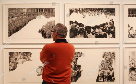 An attendee of the 2013 Armory Show is shown viewing work by California artist John Baldessari, New York