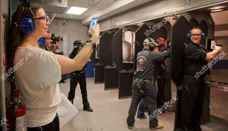 Tanya Morris, left, takes a photo of her new husband, Ted Morris on the shooting range after getting married at the Guns and Ammo Garage, in Las Vegas. Never known for its understatement or good taste, Sin City is bucking the national trend of avoiding flippant gun promotions after the Newton, Conn., elementary school shooting. Instead, it is embracing tourists' newfound interest in big guns the only way it knows how: by going all in
