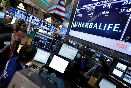 A pair of specialists confer at the post that handles Herbalife on the floor of the New York Stock Exchange . Dietary supplements company Herbalife will add two new members to its board of directors at the request of billionaire investor Carl Icahn, who has backed the company in a public spat with hedge fund manager Bill Ackman