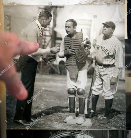 "Henry Thomas Shows Henry (Hank) Thomas pointing to a 1924 photograph of his grandfather, Washington Senators pitching great Walter Johnson, left, talking with actor Douglas Fairbanks, center, and New York Yankees great Babe Ruth, right, that hangs on the wall of his mother's home, Carolyn Thomas, in Washington. The family is auctioning items including the personalized framed copy of Johnson's plaque from his Hall of Fame induction, a handwritten congratulatory letter from Ty Cobb, the ""Notice to Player of Release or Transfer"" signed by Senators owner Clark Griffith after Johnson's final season in 1927, and an engraved six-piece tea set celebrating the 20th anniversary of Johnson's signing with the team next weekend"