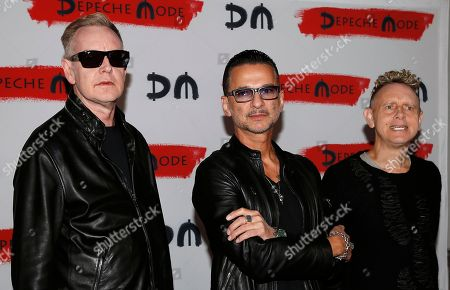 Stock Image of From left, Andrew Fletcher, Dave Gahan and Martin Gore, of the British band Depeche Mode, pose for photographers prior to the start of a press conference to promote their upcoming tour and new album in Milan, Italy