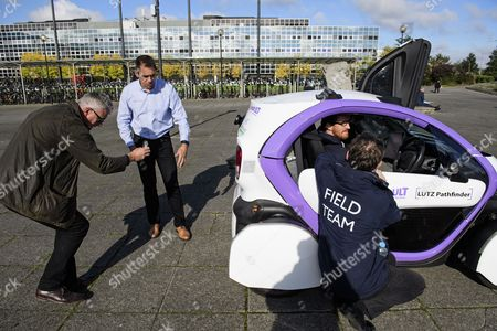 Dr Graeme Smith, CEO and chairman of Oxbotica (second left, blue shirt)) watches over as driverless cars are tested around pedestrian areas in Milton Keynes in the first public test of autonomous electric vehicles in the UK