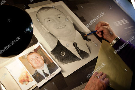 Artist Michael Reagan works on a portrait of Joseph A. Weems, who died after being after being hit by a train while riding his bicycle near the Ramstein Air Base in Germany as he served in the U.S. Air Force, at his home in Edmonds, Wash. Since starting the Fallen Heros Project in 2004, Reagan has drawn more than 3,000 portraits and given them free-of-charge to families of fallen soldiers