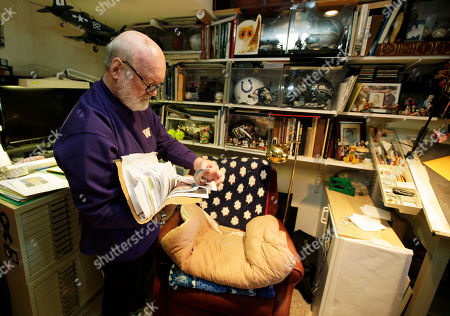 Artist Michael Reagan leafs through a file of family photos he has used to draw portraits of men and women who have been killed at war, at his home in Edmonds, Wash. Since starting the Fallen Heros Project in 2004, Reagan has drawn more than 3,000 portraits and given them free-of-charge to families of fallen soldiers