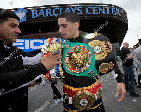 Danny Garcia, Angel Garcia Boxer Danny Garcia, right, from Philadelphia, the current Ring Magazine, WBC and WBA Super Lightweight Champion, wears his belts, assisted by trainer Angel Garcia, outside the Barclays Center, in the Brooklyn borough of New York, . Garcia is scheduled to defend his titles against Erik Morales, of Tijuana, Mexico, Saturday night at the venue