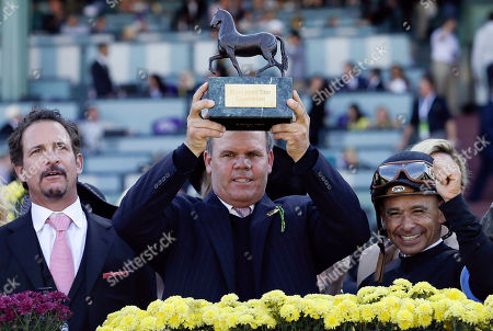 Mike Puype, Jim Rome, Mike Smith Trainer Mike Puype, center, holds up the trophy in the winner's circle as owner Jim Rome, left, and jockey Mike Smith, right, look on after Mizdirection won the Breeders' Cup Turf Sprint horse race, at Santa Anita Park in Arcadia, Calif