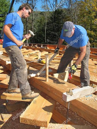 Ryan James, left, of Swanzey, N.H., prepares to drive a connecting dowel into wooden beams on in Bartonsville, Vt., after his father Steven James, right, also of Swanzey, finished boring the hole. The James' are working on the reconstruction of the covered bridge over the Williams River that was destroyed last year by Tropical Storm Irene