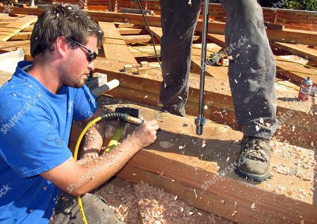 Ryan James, of Swanzey, N.H., clears wood shavings from a hole being bored into wooden beams by his father, Steven James, in Bartonsville, Vt., The James' are working on the reconstruction of the covered bridge over the Williams River that was destroyed last year by Tropical Storm Irene