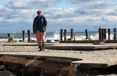 Peter Green surveys the wreckage of an oceanfront home in Bay Head N.J., two days after Superstorm Sandy hit. A group of Bay head oceanfront homeowners is suing the state, seeking to be exempted from a statewide project to construct protective sand dunes along New jersey's entire 127-mile coastline, saying that a roick wall they built themselves works better than dunes