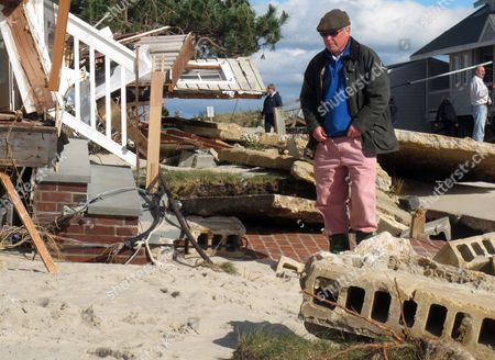 Peter Green looks at the wreckage of his oceanfront home in Bay Head N.J.,two days after Superstorm Sandy hit. A group of Bay Head oceanfront homeowners is suing the state, seeking to be exempted from a statewide project to construct protective sand dunes along New jersey's entire 127-mile coastline, saying that a rock wall they built themselves works better than dunes