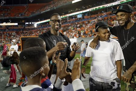 Dwyane Wade, Udonis Haslem Miami Heat's Dwyane Wade, center, and Udonis Haslem, right, stand on the sideline as boys make the The U sign before an NCAA college football game against Florida State, in Miami