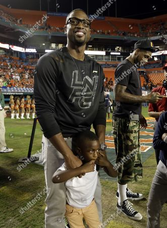 Dwyane Wade, Zion Wade, Udonis Haslem The Miami Heat's Dwyane Wade stands with his son Zion before an NCAA college football game between Miami and Florida State, in Miami. At right is Udonis Haslem of the Heat