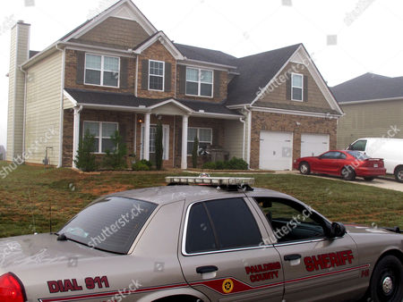 A Paulding County sheriff's deputy sits, outside the suburban home in Dallas, Ga., about 30 miles outside Atlanta, where authorities say Paul and Sheila Comer kept their 18-year-old son in a bedroom for about two years before the emaciated teenager was placed on a bus to Los Angeles by his stepfather. Los Angeles police said the teen told officers his stepfather gave him $200 and a list of homeless shelters before he was put on a bus to California on his 18th birthday. The couple faced charges of false imprisonment and cruelty to children, Paulding County jail records show. (AP Photo/Russ Bynum