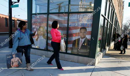 Residents of Chicago's 7th Ward and Illinois' 2nd Congressional District walk past the shared offices of Alderman Sandi Jackson and her husband former US Rep. Jesse Jackson Jr., in Chicago. Congressman Jackson tenured his resignation to House Speaker John Boehner citing his battle with bipolar disorder and separate federal investigations