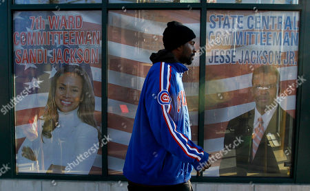 A lone resident of Chicago's 7th Ward and Illinois' 2nd Congressional District walk past the shared offices of Alderman Sandi Jackson and her husband former US Rep. Jesse Jackson Jr., in Chicago. Congressman Jackson tenured his resignation to House Speaker John Boehner citing his battle with bipolar disorder and separate federal investigations
