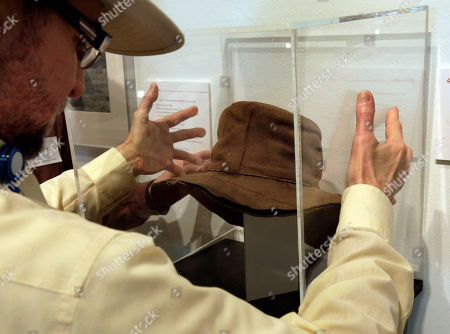 """Museum Installer Rene Ronda places a protective plexiglass cube cover over a hat by designer by Edith Head, from the 1975 movie """"Rooster Cogburn,"""" as part of the """"Katharine Hepburn: Dressed for Stage and Screen"""" exhibit in the New York Public Library for the Performing Arts at Lincoln Center"""