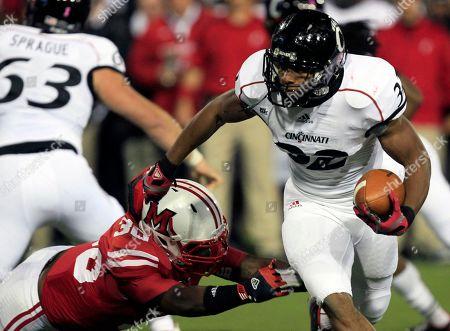 Evan Harris, George Winn Cincinnati running back George Winn (32) avoids a tackle by Miami (Ohio) linebacker Evan Harris (30) in the first half of an NCAA college football game, in Cincinnati