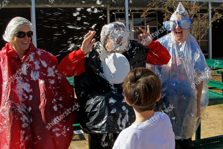 Karen Schmidt, Amanda Stocks, Sue Townsend, Blake Mitchell Singleton Stonebridge Elementary School assistant principals Karen Schmidt, left, and Amanda Stocks, right laugh as Principal Sue Townsend, receives a direct hit from a cream pie tossed at her by Blake Mitchell Singleton, seven and a second grade student, in Brandon, Miss. The top fund raising students during a recent technology fund drive earned the opportunity to toss a cream pie at the administrators. The student body raised $8,500 that will be used to purchase more IPads and laptops for the students to use