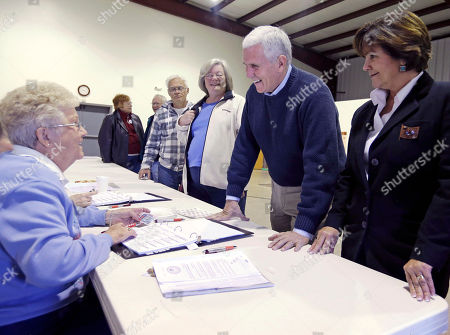 Stock Picture of Mike Pence Shirley Mitchell, left, signs in Indiana's Republican gubernatorial candidate Mike Pence, and his wife, Karen, right, to cast their votes, in Clifford, Ind. Pence is running against Democrat John Gregg and Libertarian Rupert Boneham